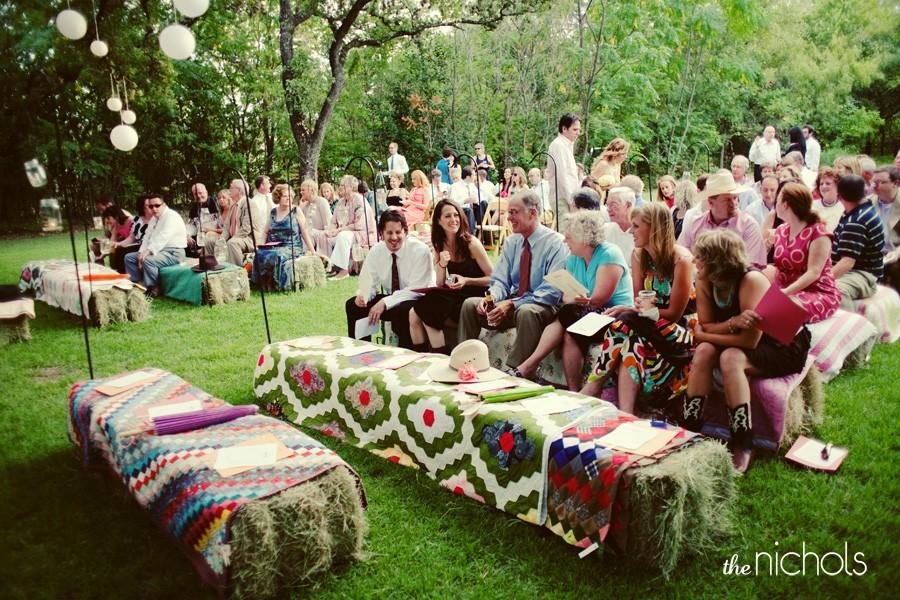 O casamento ao ar livre possibilita uma decoração extrovertida, mas charmosa. Aqui, a decoração rústica acomodou os convidados para a cerimônia em bancos feitos de feno, cobertos por panos estampados. Bem DIY, não? ;)