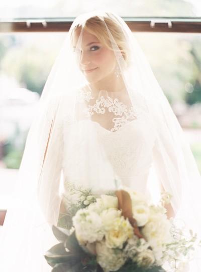 o véu enorme cobre a noiva radiante em frente à janela