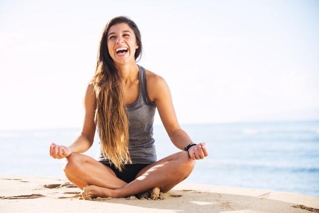 Mulher praticando yoga na praia - relaxamento e concentração para se livrar do estresse!