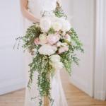 Bouquet de noiva em formato cascata feito com flores e folhas.