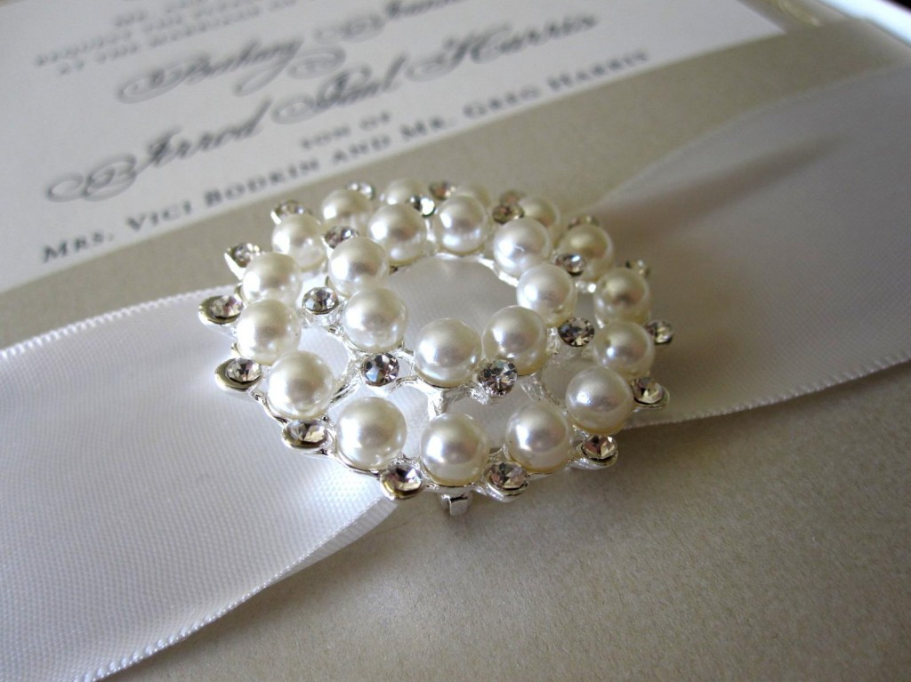 Elegante detalle en estas tarjetas de boda con cinta ancha de raso en blanco y gris perlado
