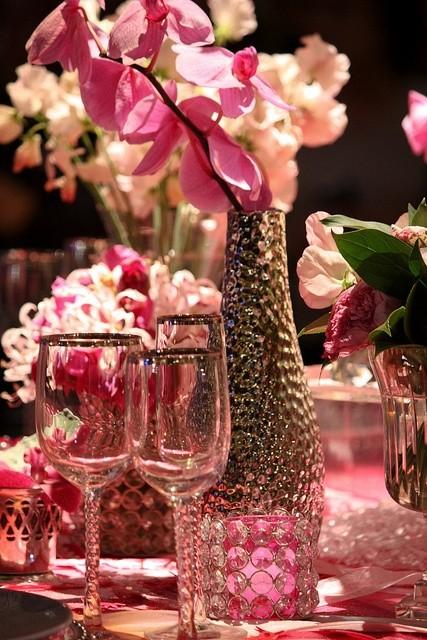 Decoración de mesa floral estilo glam. Para añadirle un toque de glamour muy especial a la decoración de salones, las copas y demás detalles de cristal pueden llevar dibujos en relieve y detalles plateados en los bordes. ¡Dejaremos que nuestra mesa se inunde de brillo y diferentes tonalidades en rosa, ya que siempre son  bienvenidas!