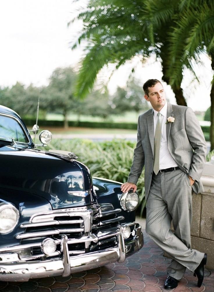 Novio con traje gris acompañado de un coche de época