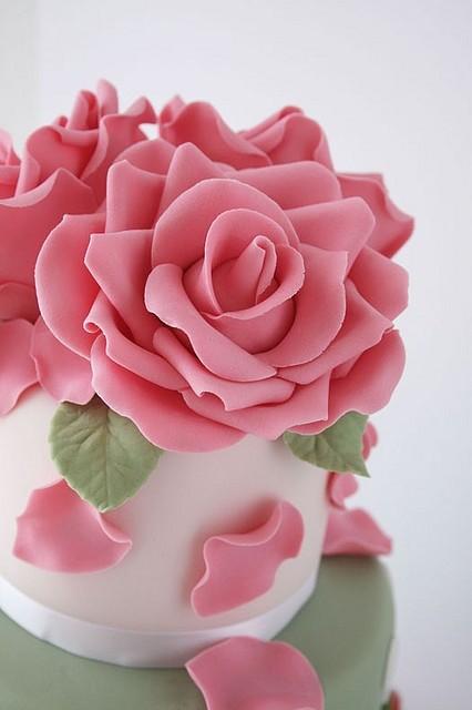 Mini cake de rosa hecha en fondant sobre pastel blanco