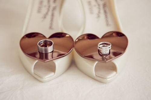 Las alianzas de boda presentadas sobre los zapatos de la novia