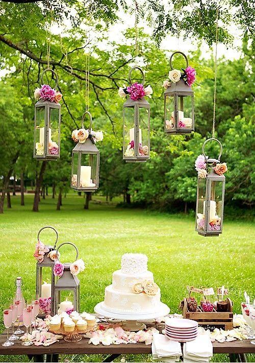 Mesa de tarta nupcial en un jardín, adornada de preciosos farolillos con velas y flores