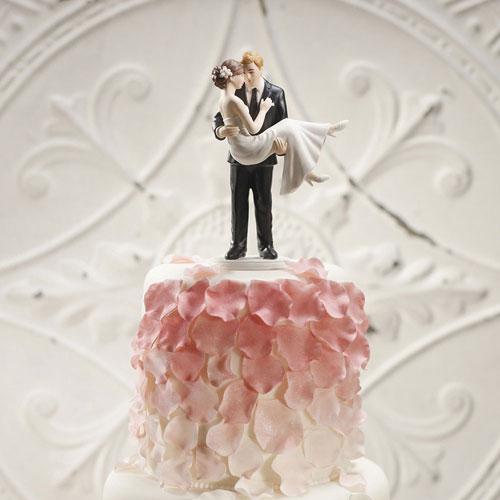 Una figura de tarta personalizada donde el novio toma a su mujer en brazos