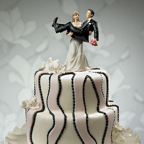 Figurita de tarta en la que se han cambiado los papeles y es la novia quien lleva al novio