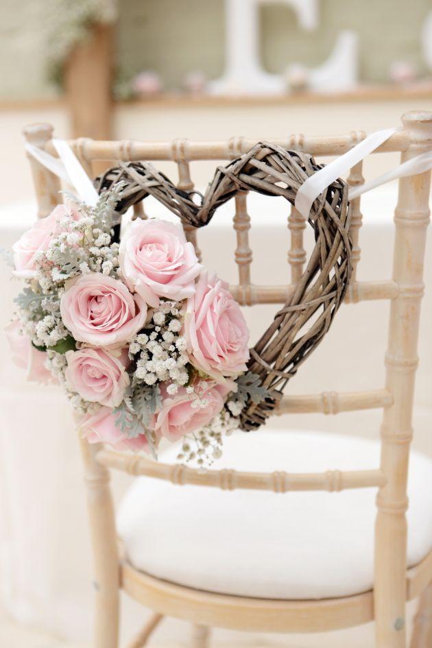 Corazón para decorar las sillas de boda hecho con ramas y rosas