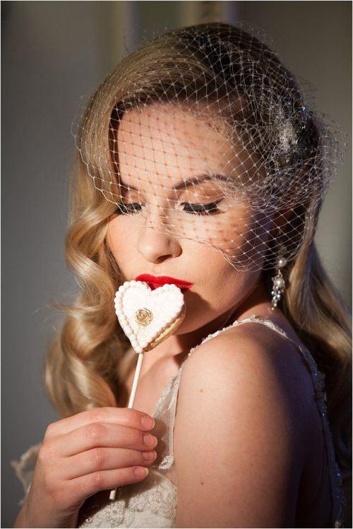 Ondas vintage, tocado de rejilla y labios rojos para una novia muy moderna
