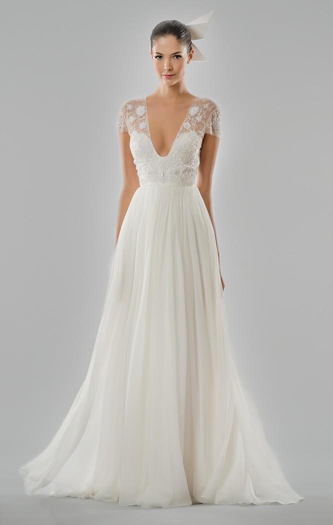 El escote a pico y la falda plisada hacen de este traje de novia toda una belleza