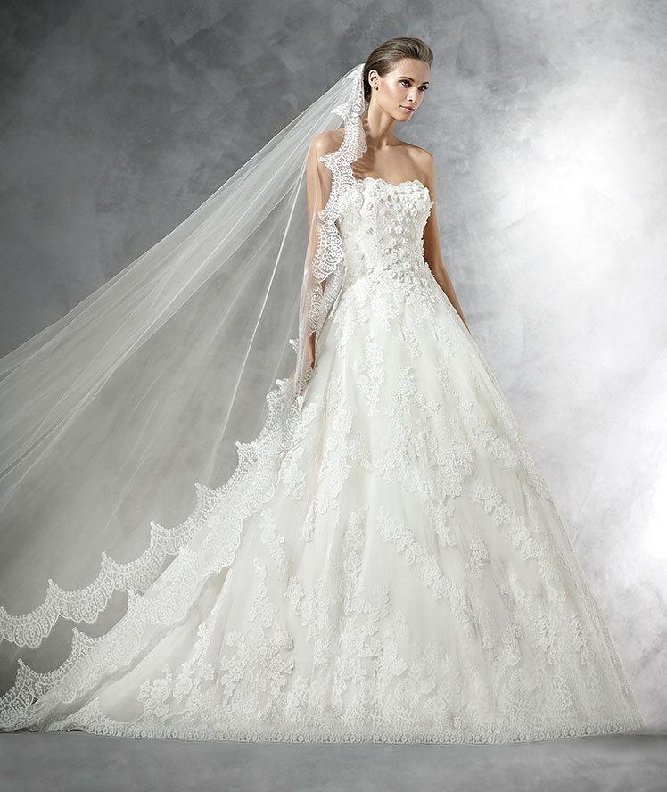 Prometea se viste con un vestido de novia evasé y capas ligeras de Pronovias