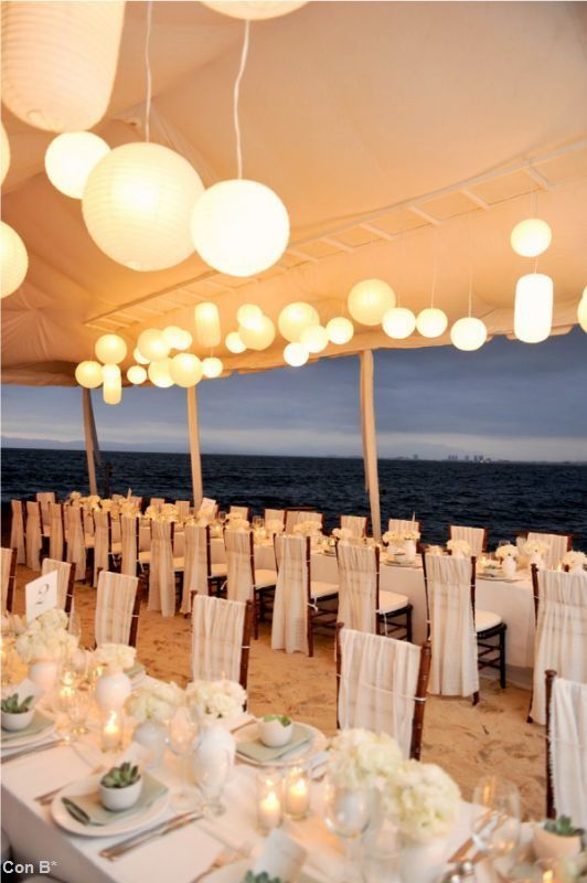 Mesas decoradas en blanco con carpa y luces para bodas en la playa