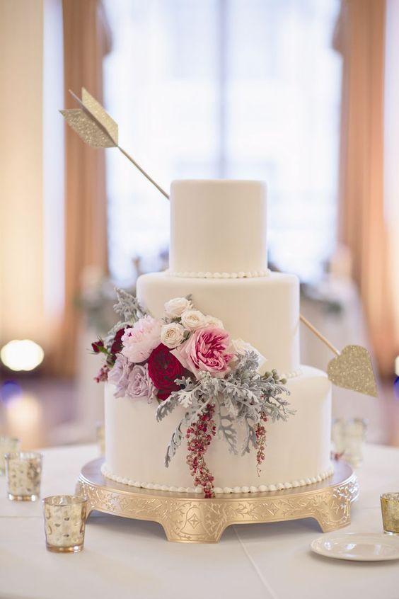 Una tarta de boda adornada con flores y una flecha